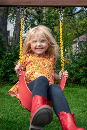 Portrait of a girl sitting on swing at playground