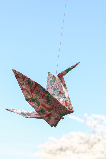 Low angle view of paper crane against clear blue sky
