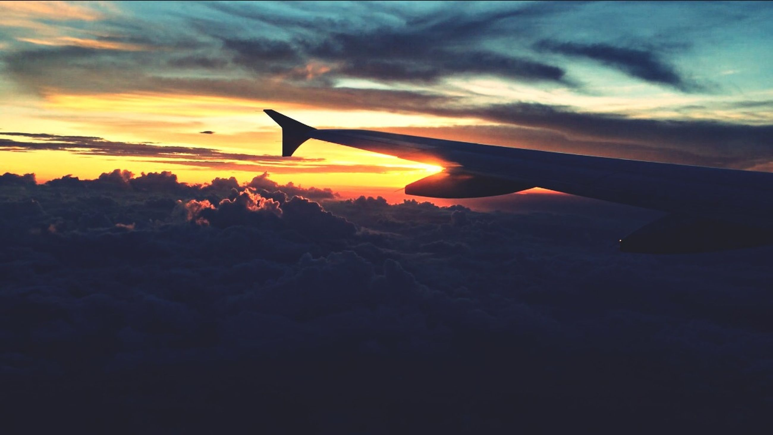 airplane, flying, air vehicle, aircraft wing, transportation, mode of transport, sunset, sky, mid-air, aerial view, part of, cloud - sky, scenics, travel, landscape, public transportation, beauty in nature, cropped, on the move, journey