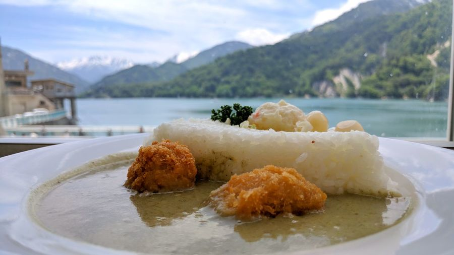 Close-up of bread in plate on table by lake against sky
