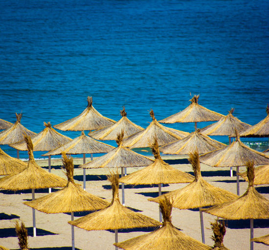 Deck chairs and parasols on beach against blue sea