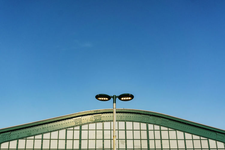 Low Angle View Of Street Light By Building Against Blue Sky