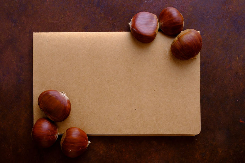 Chestnuts on the table with copy space Chestnuts Copy Space Menu Agenda Blank Brown Chestnut Close-up Food Food And Drink Freshness Fruit Healthy Eating Indoors  Ingredient No People Notebook Nut Nut - Food Paper Red Still Life Table Wellbeing Wood - Material