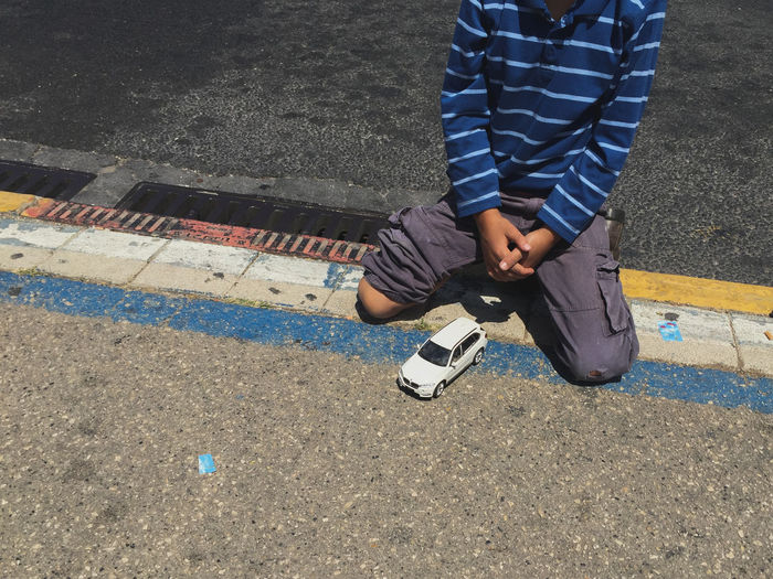 Low section of boy kneeling by toy car on footpath