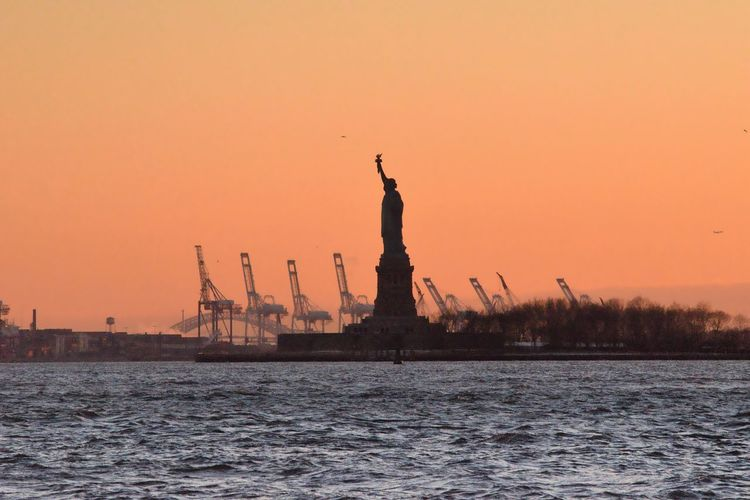 Statue Of Liberty And Sea Against Orange Sky During Sunset