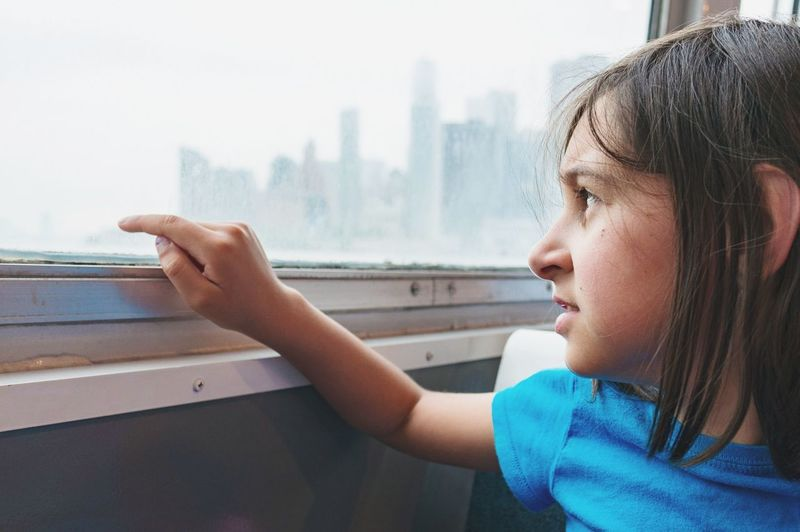 Close-Up Of Girl Looking At Window In Ferry