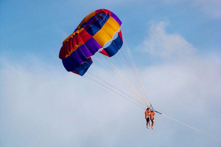 Low Angle View Of Couple Parasailing Against Sky