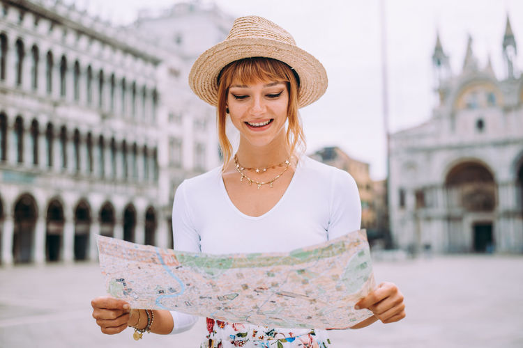 Smiling woman holding map standing against building