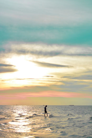 Digital composite image of silhouette man walking on sea at sunset