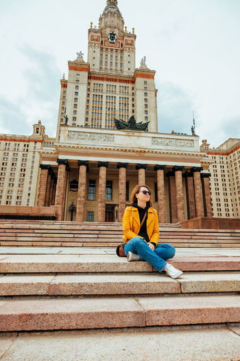 Full length of woman sitting on staircase in city against sky