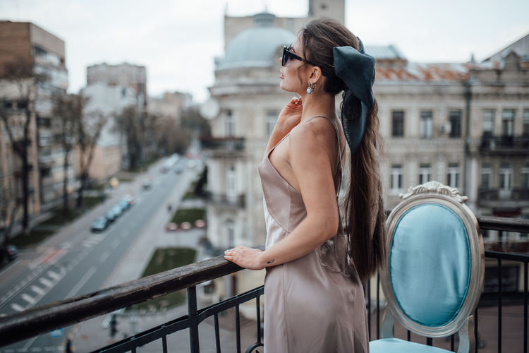 Side view of young woman standing on railing in city