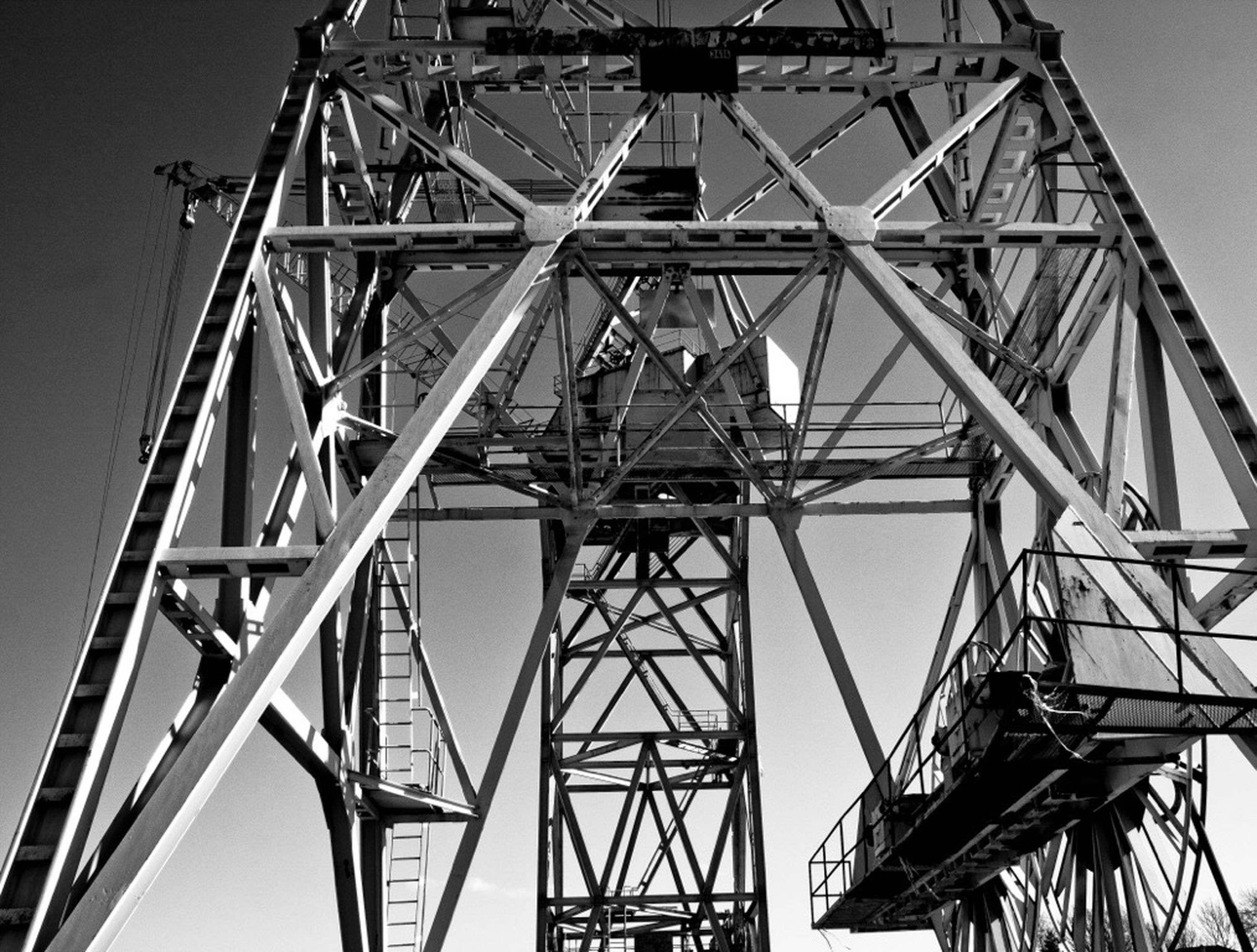 low angle view, metal, built structure, connection, metallic, sky, architecture, engineering, construction site, development, clear sky, construction, outdoors, day, no people, electricity pylon, fuel and power generation, tall - high, crane - construction machinery, grid