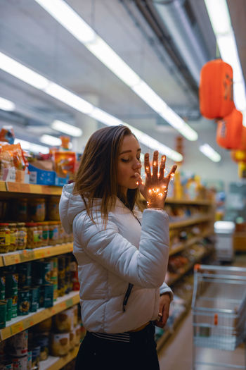 Young Woman Holding Illuminated String Light In Supermarket