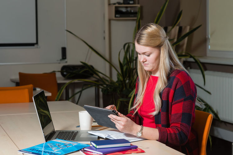Young Woman Using Digital Tablet On Desk At Home
