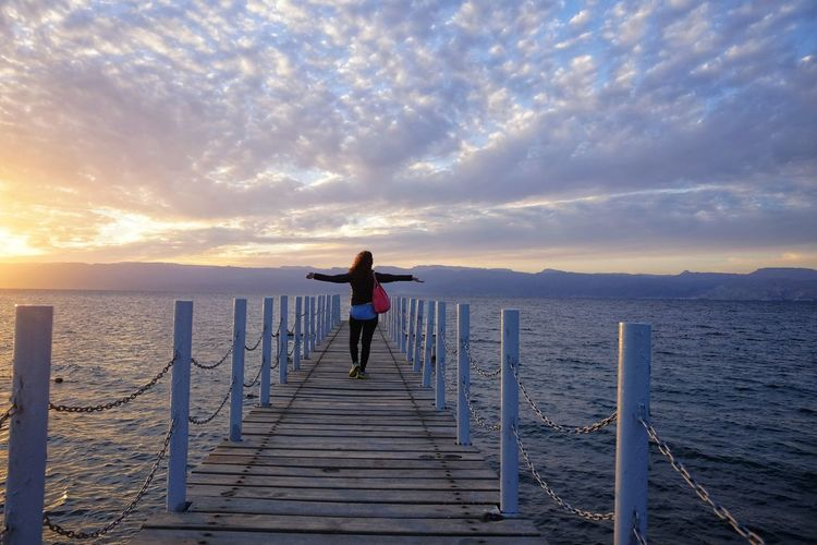 girl on the catwalk at sunset Sky Sea Water One Person Rear View Beauty In Nature Scenics - Nature Cloud - Sky Standing Sunset Pier Real People Lifestyles Leisure Activity Full Length Nature The Way Forward Direction Horizon Over Water Outdoors Looking At View Human Arm Woman Red Red Sea