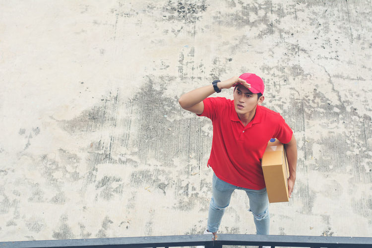 High angle view of delivery man holding package while standing on footpath