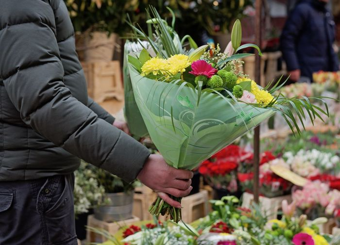Flower marked A Bouquet Of Flowers Flower Market Freshness Man Bouquet Close-up Day Flower Shopping Flowers For Sale Gift Human Hand Real People Retail  Sales