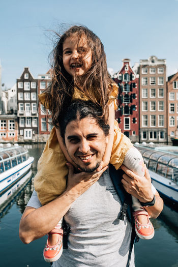 Portrait of friends standing at canal in city