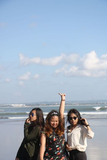 Woman gesturing while standing with friends at beach against sky