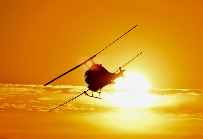 Dusting crops at sunset in California's Imperial Valley Sunset Orange Color Silhouette Helicopter Cropduster Cropdusting Aircraft
