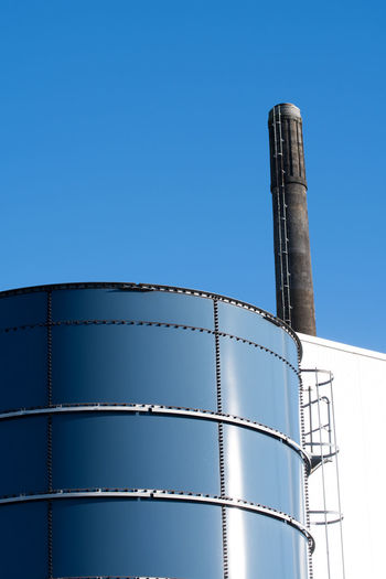Low angle view of factory against clear blue sky