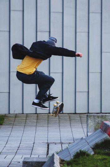 Full length of man skateboarding against wall