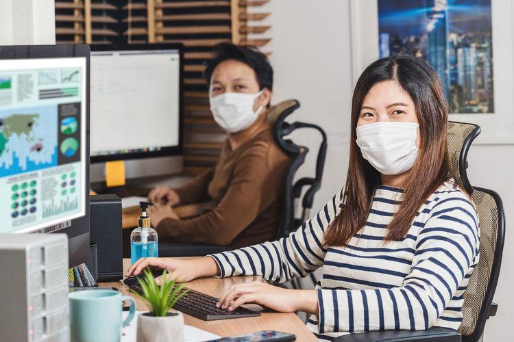 Portrait of business people wearing mask in office