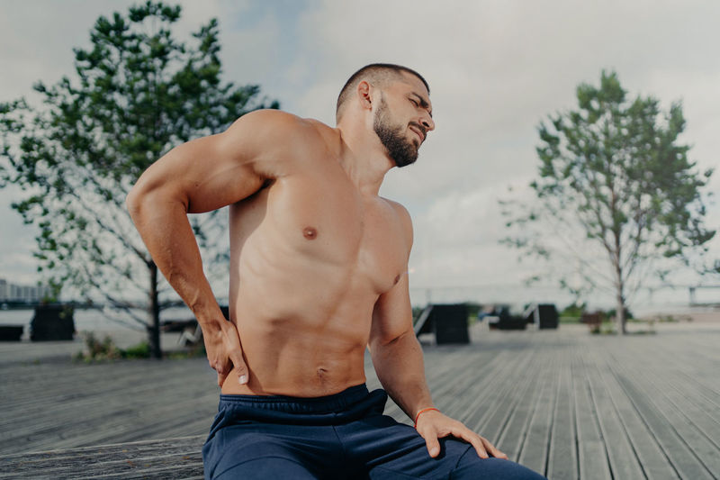 Shirtless man with backache sitting outdoors