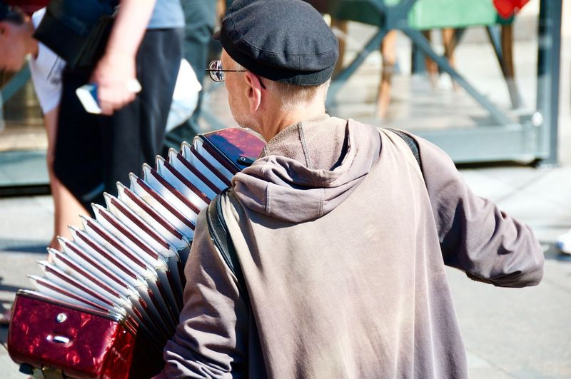 Man playing accordion while standing in city