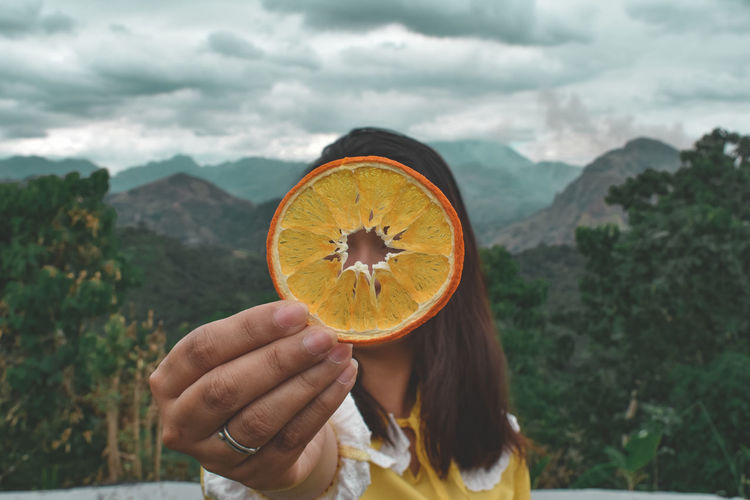 Woman holding slice of orange against mountains