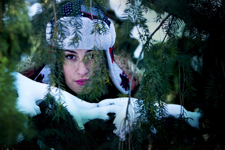 Portrait of beautiful woman standing by snow covered plants