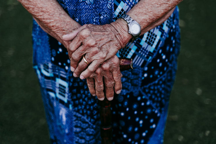 Midsection of senior woman holding walking cane