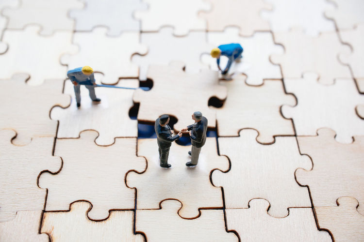 High angle view of figurines on wooden jigsaw puzzle