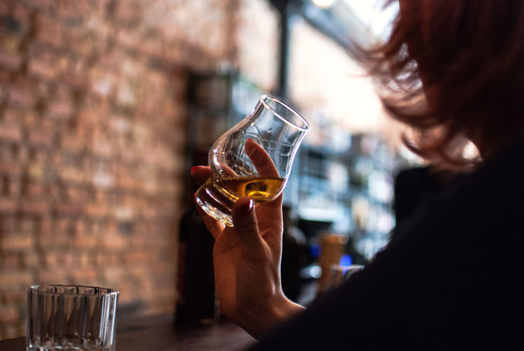 Cropped Image Of Woman Drinking Whiskey At Table In Bar