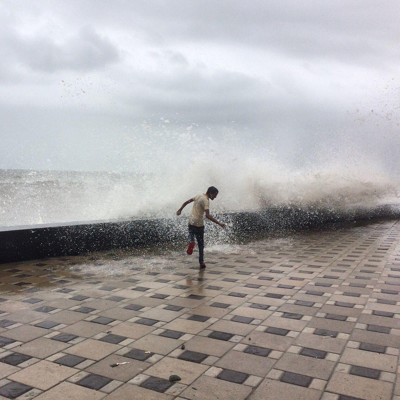 Rear view of boy enjoying by waves splashing at promenade against cloudy sky