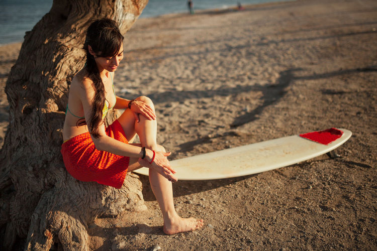 Woman sitting on tree trunk at beach