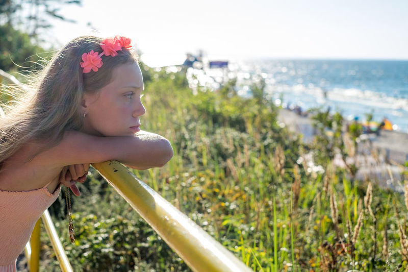 Profile View Of Thoughtful Girl Leaning On Railing At Beach