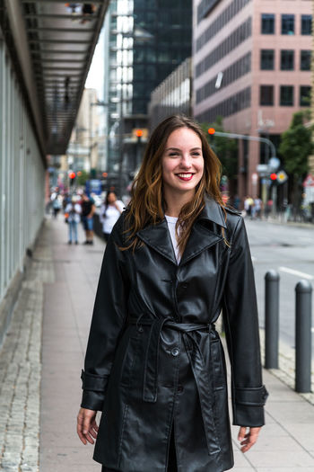 Portrait of young woman wearing a trench coat in city One Person Looking At Camera Beautiful Woman Trench Coat Fashion Beauty Lipstick Attractive Woman Urban Caucasian Young Adult Outdoors Day Autumn Brunette Architecture City Focus On Foreground Real People Smiling Front View Portrait
