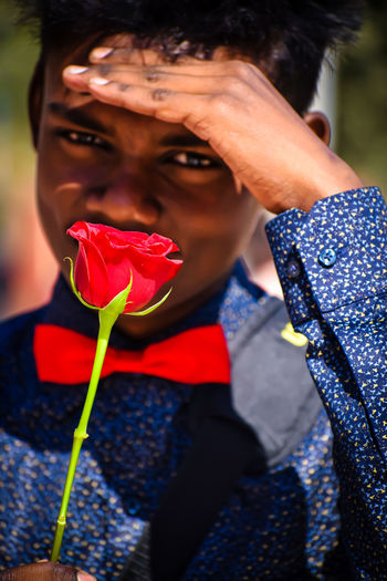 Close-up portrait of smiling man holding red rose