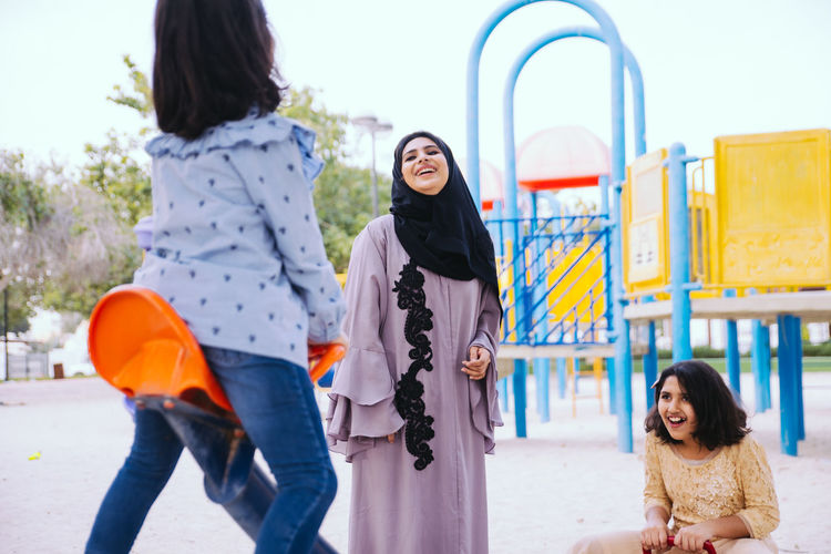 Mother with cheerful daughters enjoying at park