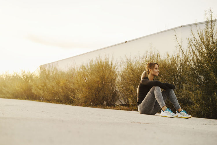 Young woman sitting on a ground after her workout, taking rest Relaxing Casual Clothing Day Full Length Land Leisure Activity Lifestyles Looking Nature One Person Outdoors Plant Real People Relaxation Resting Road Sitting Sky Surface Level Teenager Transportation Workout Workout Time Young Adult Young Women
