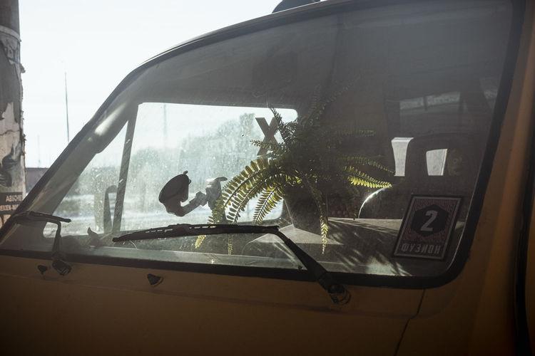 Tilt image of car seen through glass window