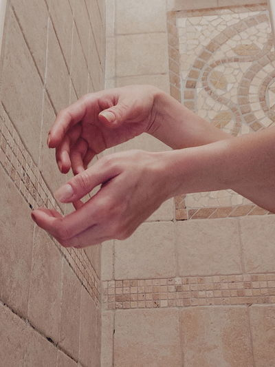 Cropped hands of woman against wall