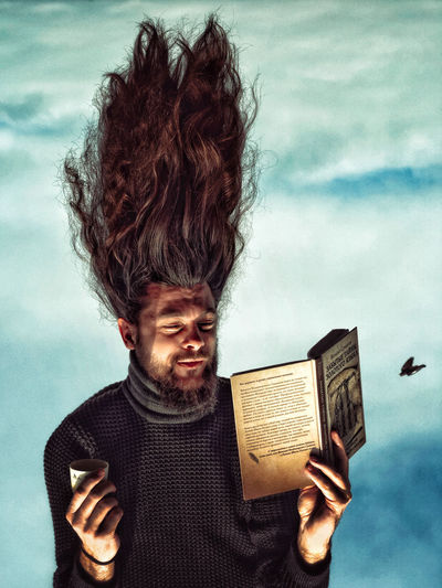 Portrait of smiling young man holding book against sky