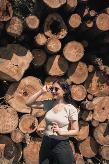 Woman holding sunglasses while standing against stack of firewood