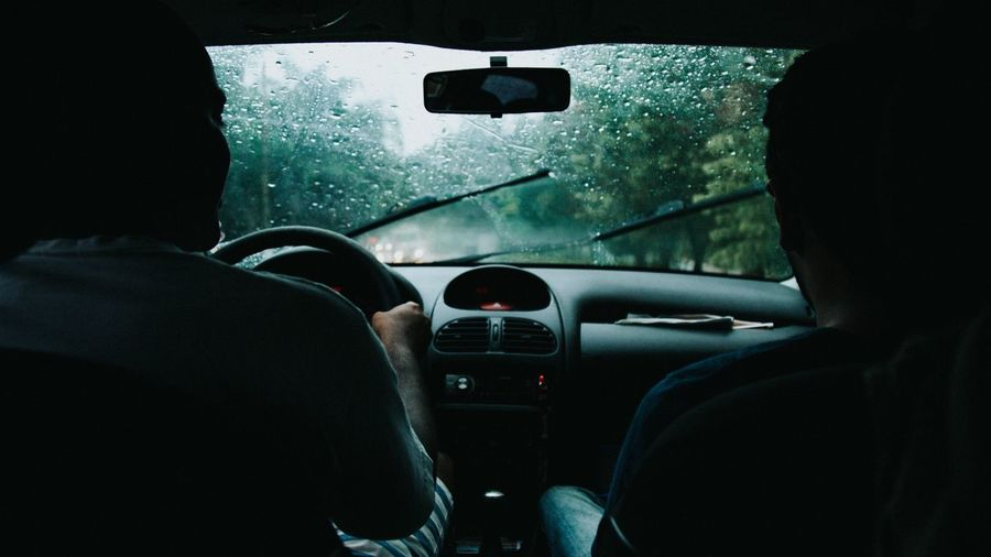 Man with friend driving car during rainy season