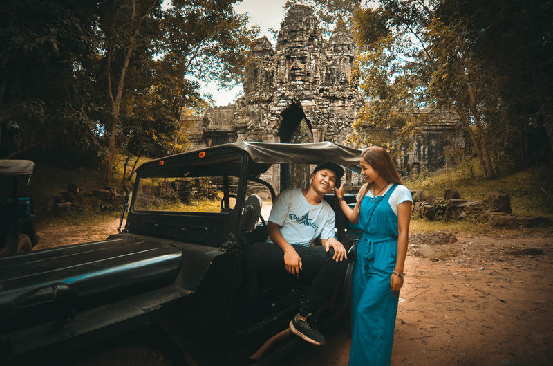 Full Length Of Couple By Vintage Car Against Trees