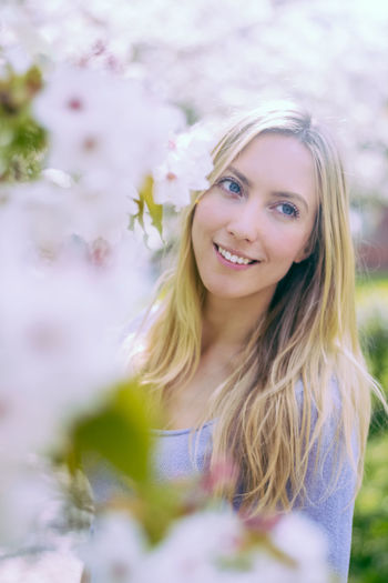 Portrait of smiling young woman against blurred background