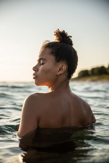 Shirtless Young Woman Swimming In Sea Against Sky