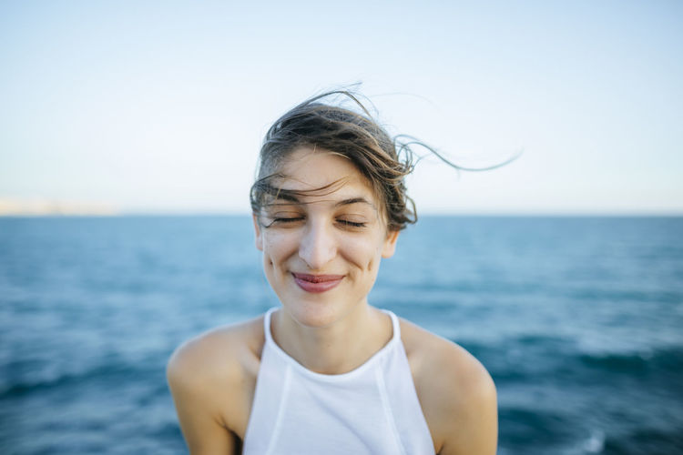 Portrait of smiling woman against sea